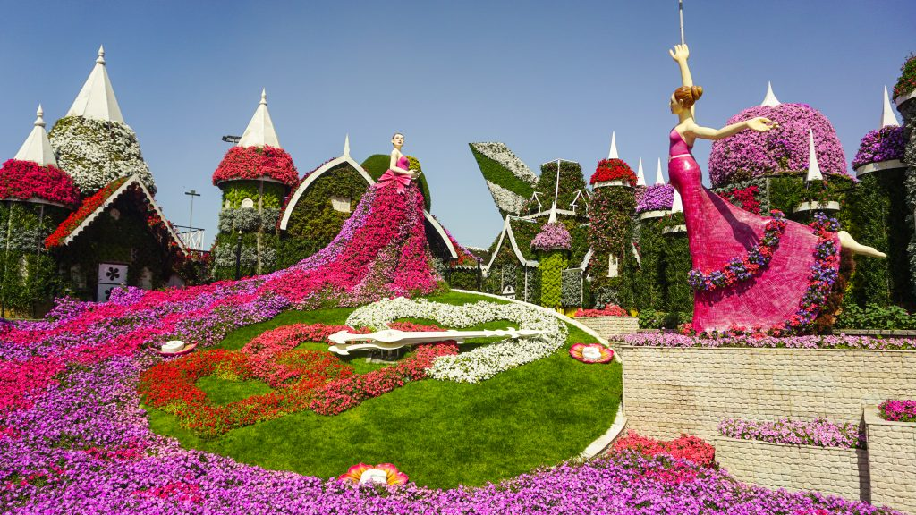 A flower clock and two dancers at Dubai Miracle Garden