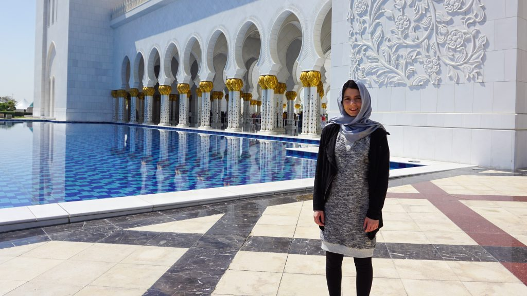 A girl standing in front of the Grand Mosque in Abu Dhabi and is covered from top to bottom