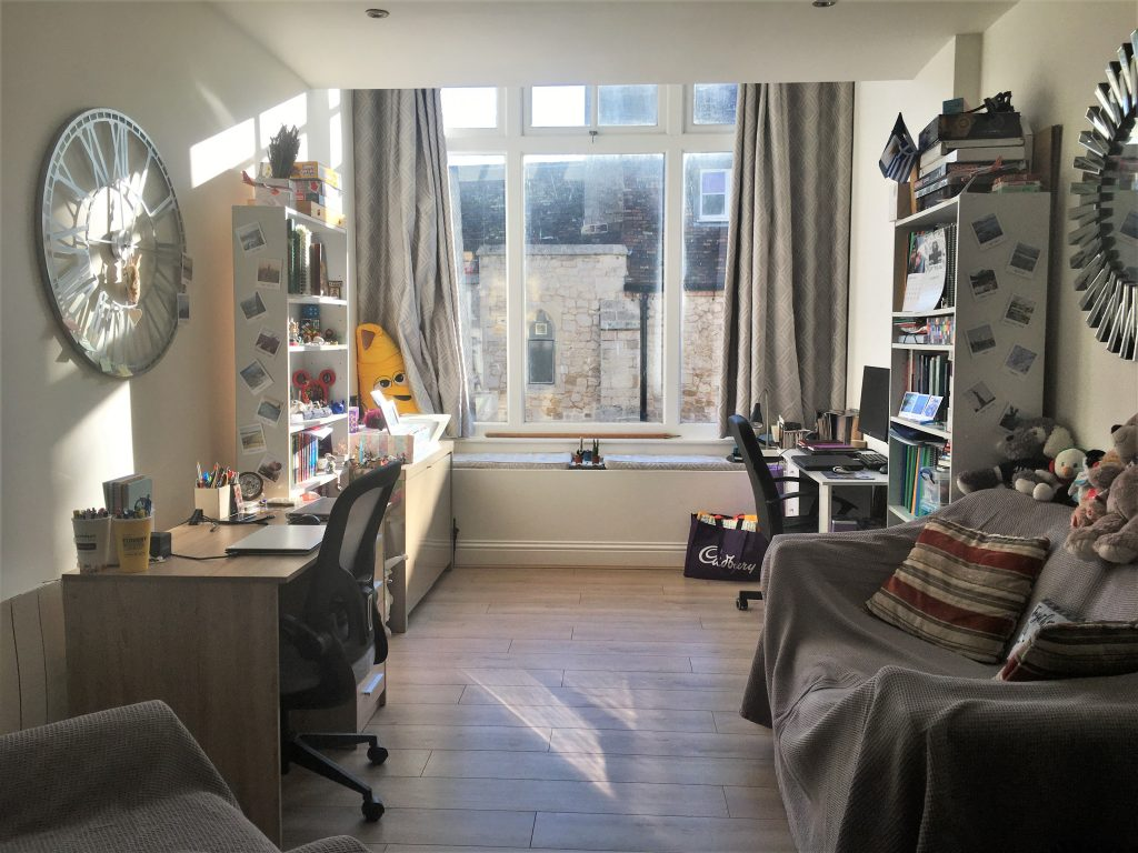 A space with two desks, two bookcases, a sofa and a window for how I spend my time at home